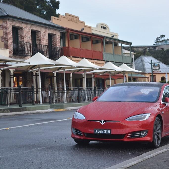 Red Tesla Electric car driving on the road near Strahan Village