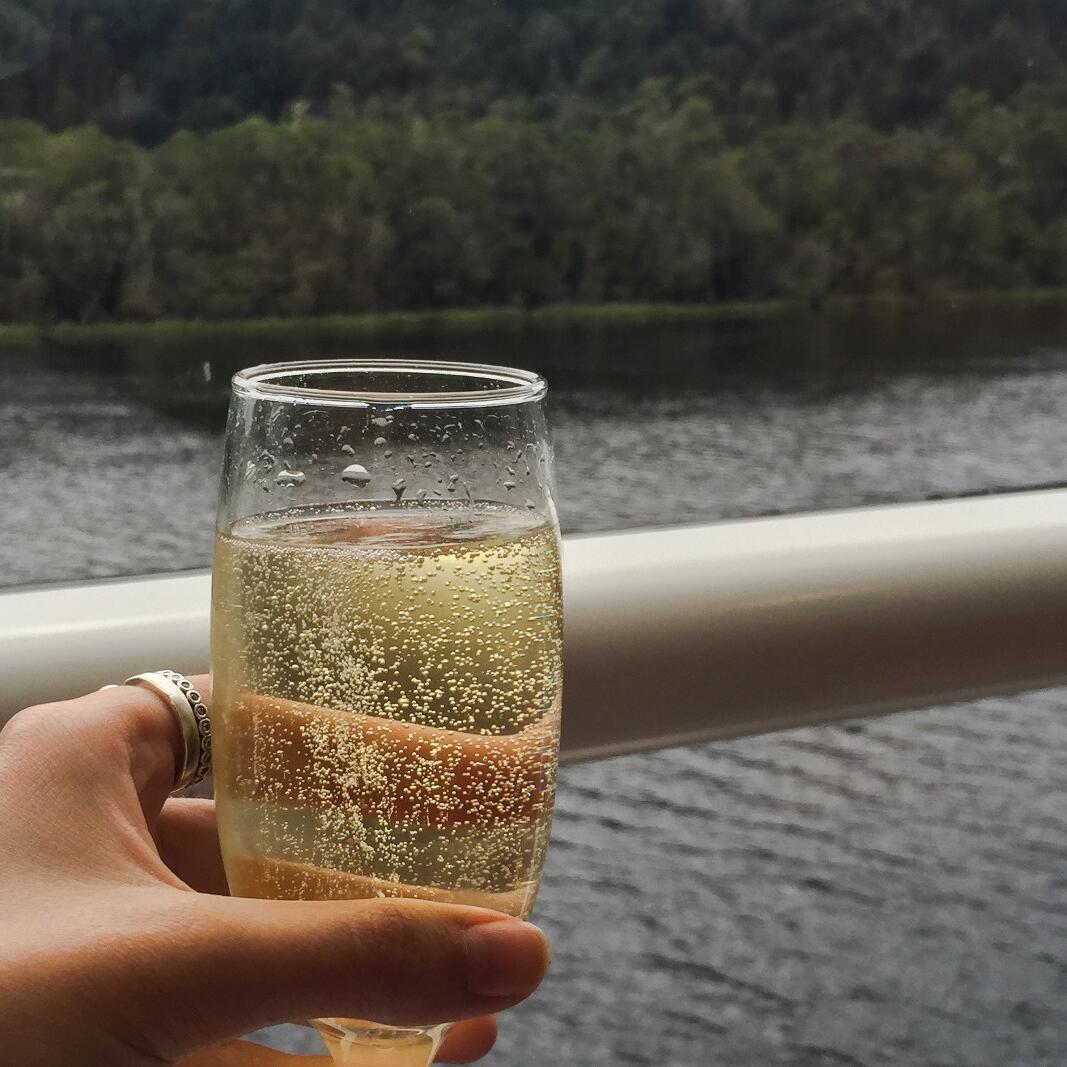 Lady holding a champagne class at the Gordon River Cruises