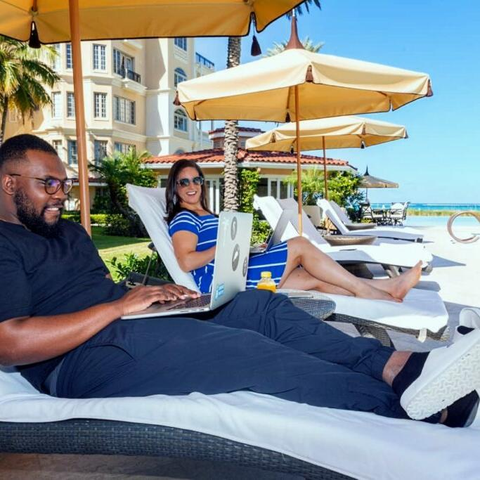 Couple on sunbeds with laptops at The Somerset on Grace Bay