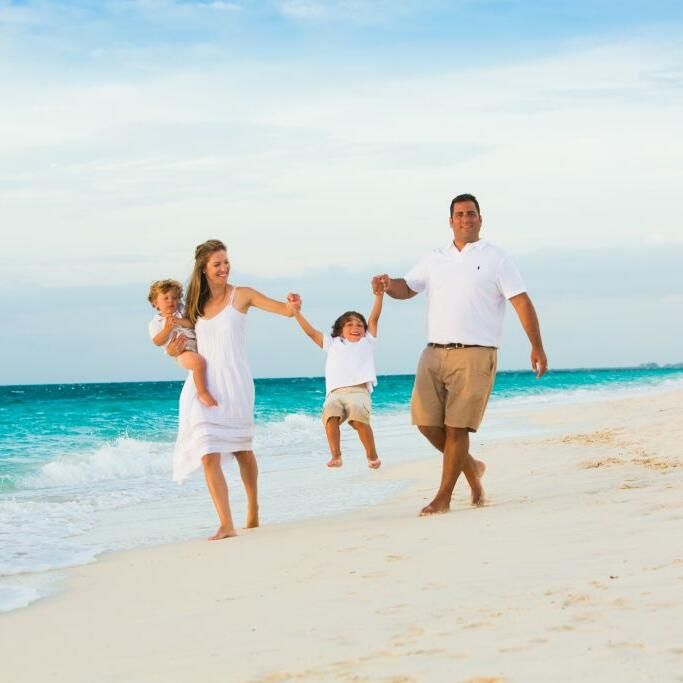 Family walking on the beach near The Somerset On Grace Bay