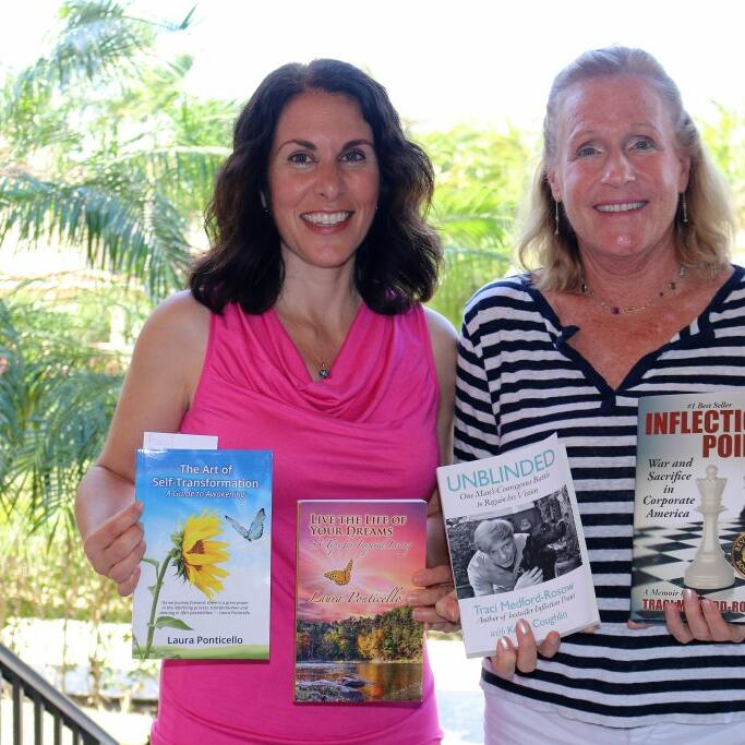 Two ladies holding books on there hands at Somerset Grace Bay