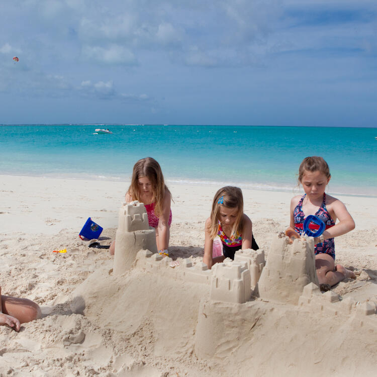 Kids building sand castle at the beach near Somerset Grace Bay