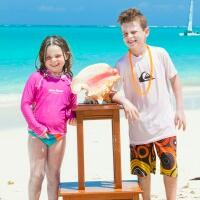 Two kids with a sea shell by the sea at Somerset On Grace Bay