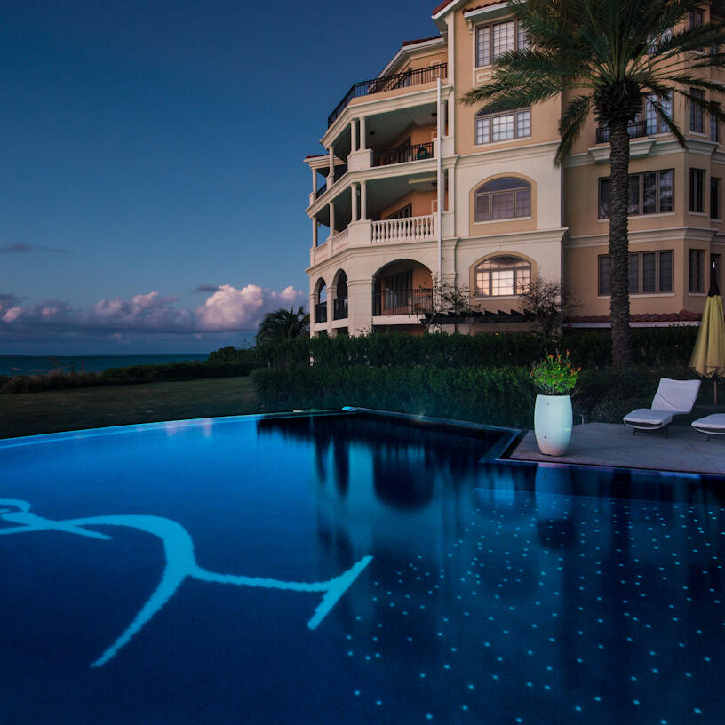 Pool at night with two sunbeds at The Somerset On Grace Bay