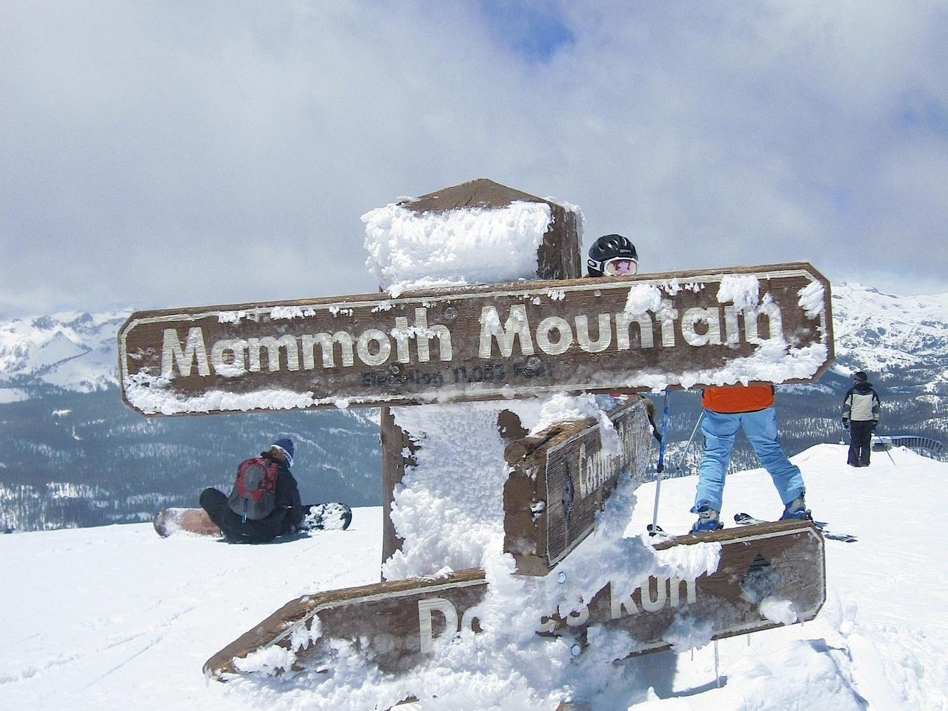 Mammoth Mountain sign covered in snow on top of mountain