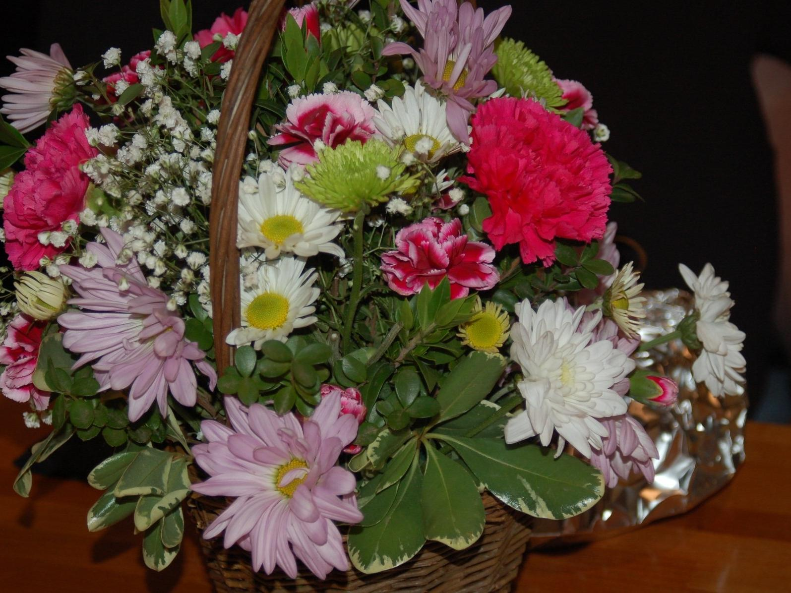 basket of pink and white carnations and assorted flowers