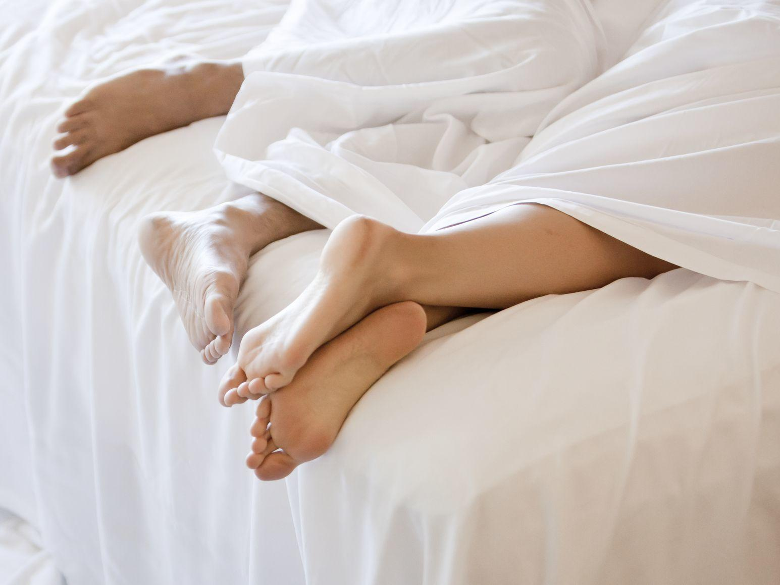 Pair of feet sticking out from white bedsheets.