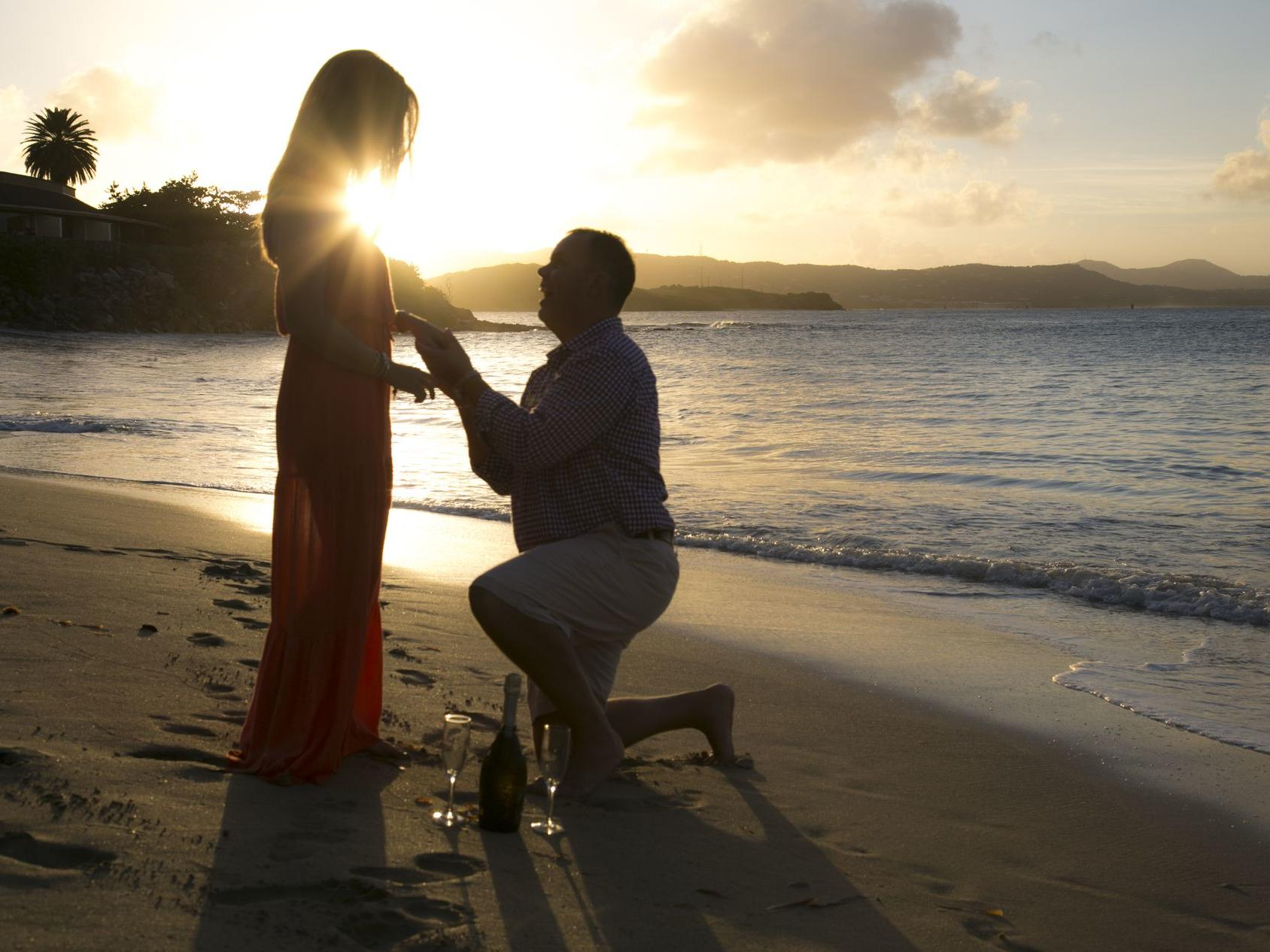 Man Proposing To Woman On Beach at Sunset