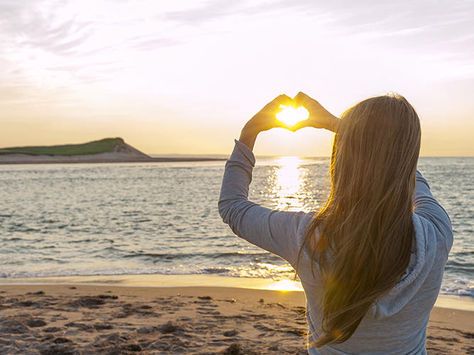 girl-on-beach-making-heart-with-hands-at-sunset