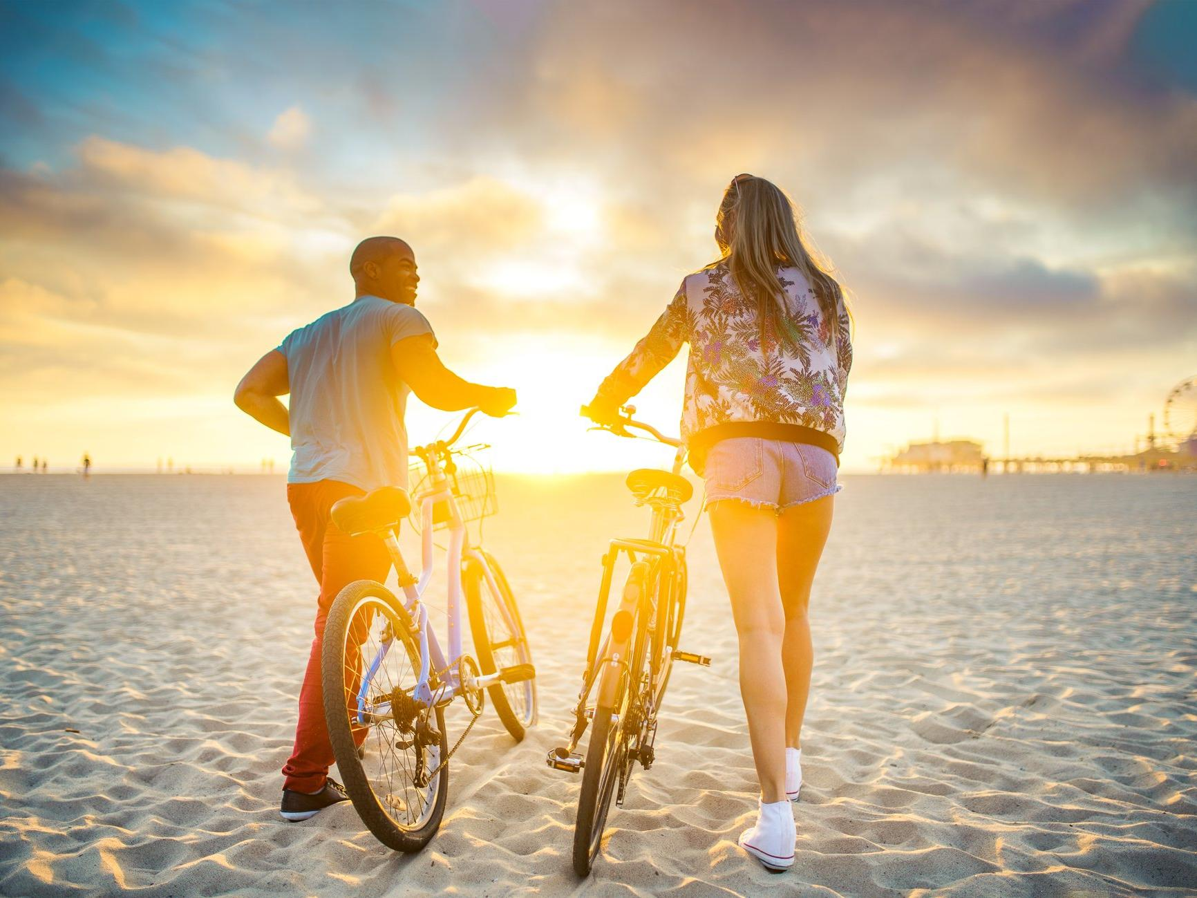 Couple walking their bikes in the sand towards a sunset