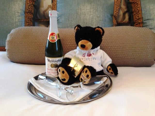 Teddy bear and bottle of sparkling cider on tray.
