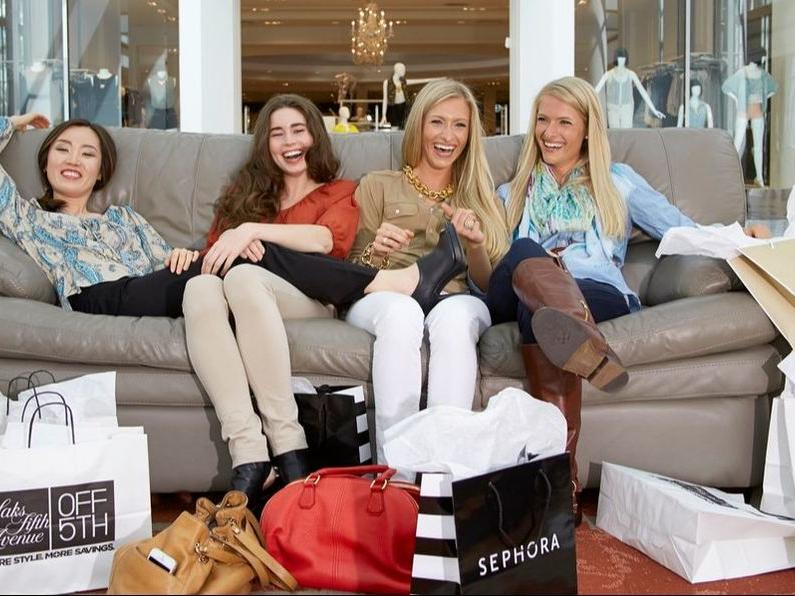 Group of women sitting on couch with several shopping bags