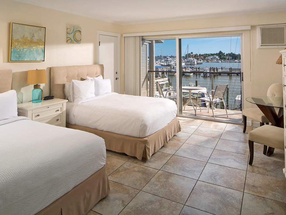 Guest room with two double beds and balcony with harbor views.