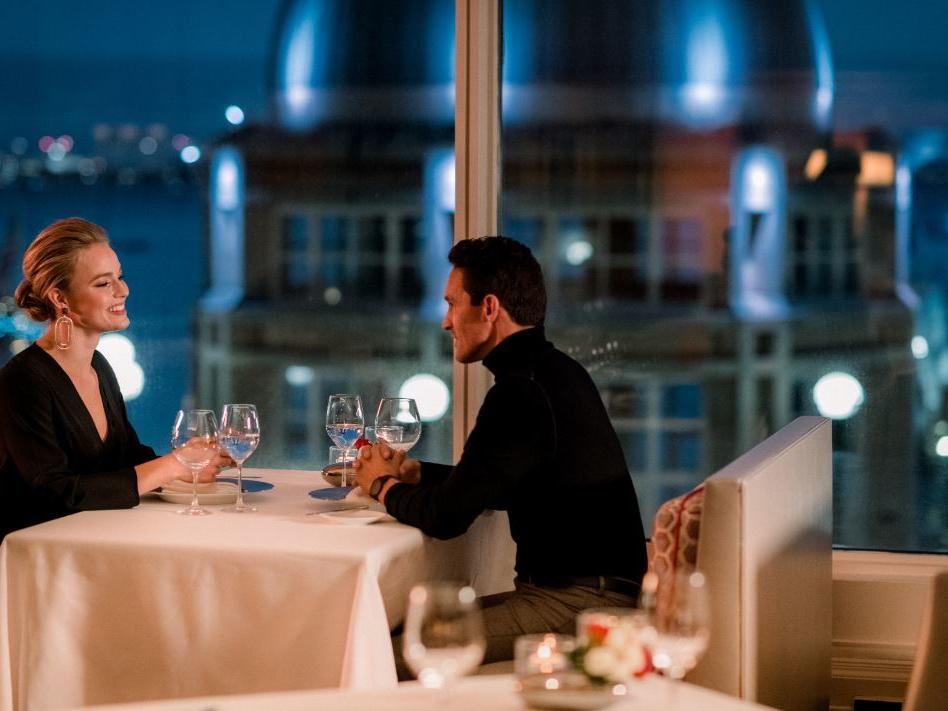 Couple drinking wine at restaurant with harbor views