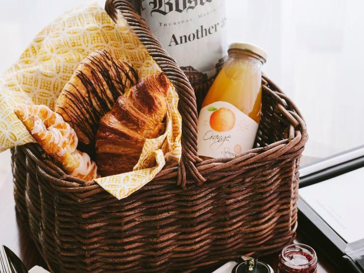 Croissants and juice in wicker basket