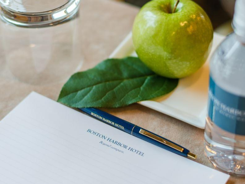 Apple and bottled water with notepad and pen