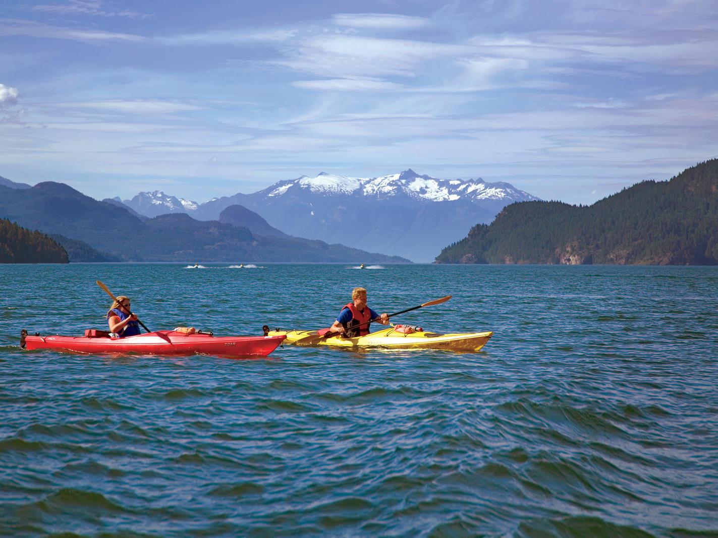People kayaking in lake with mountain views.