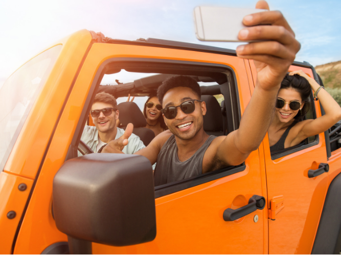 A group of friends having selfies inside a jeep