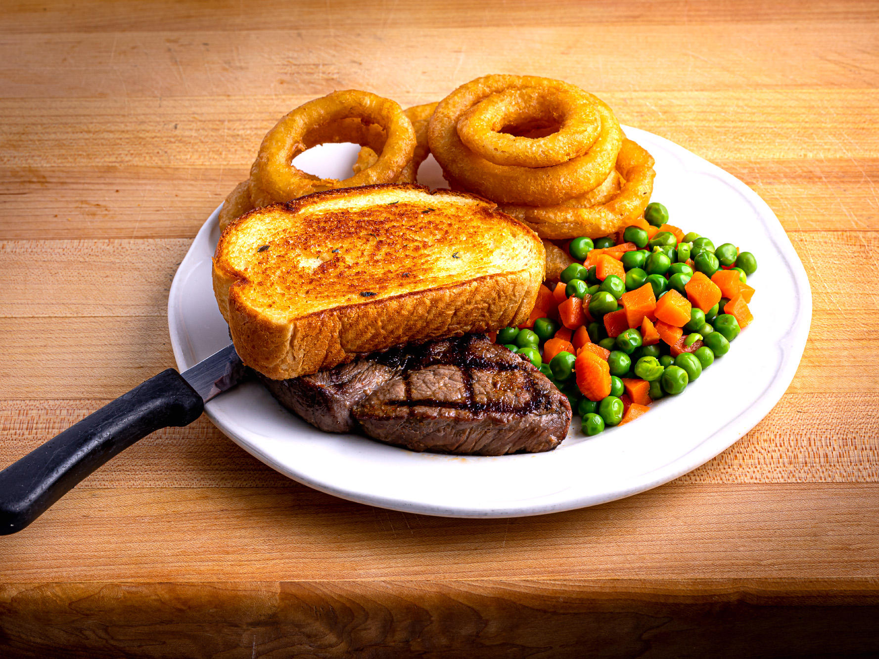 steak with onion rings, vegetables and toasted bread