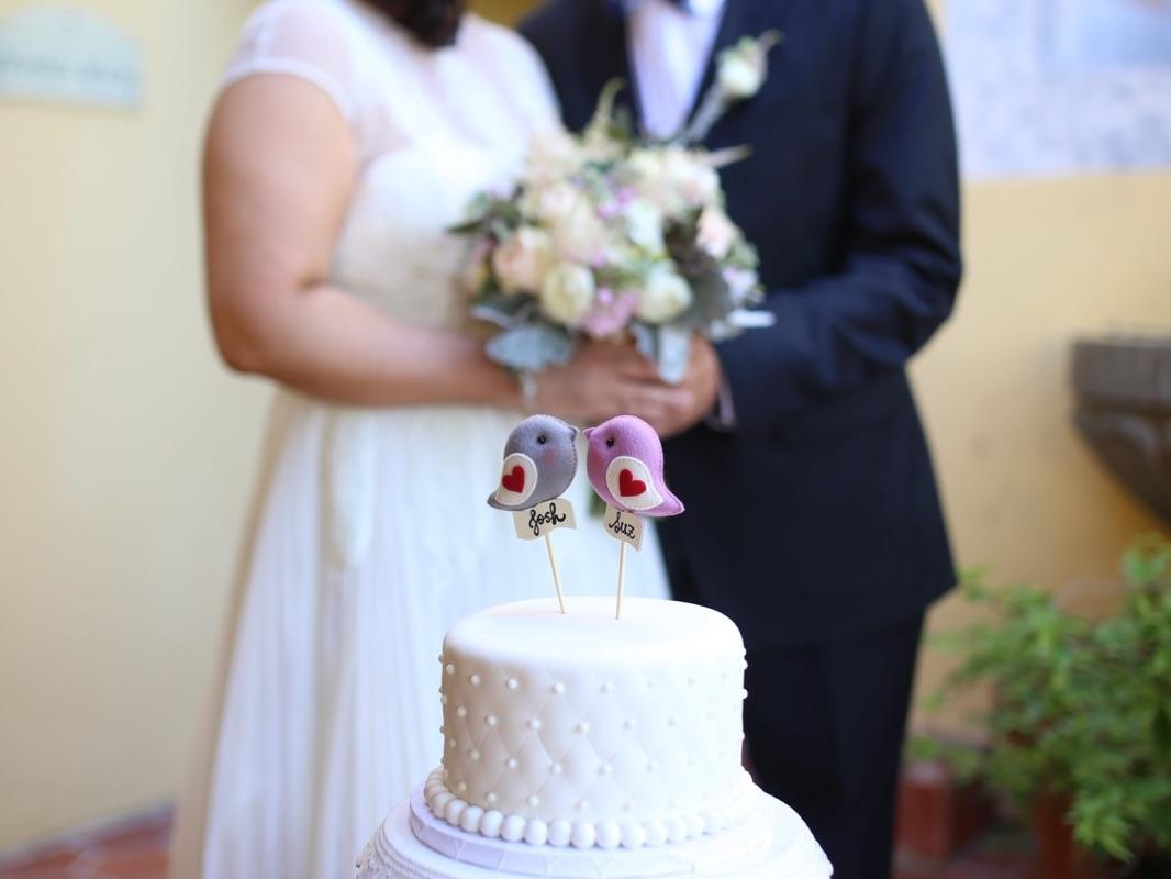 wedding couple kissing in front of cake