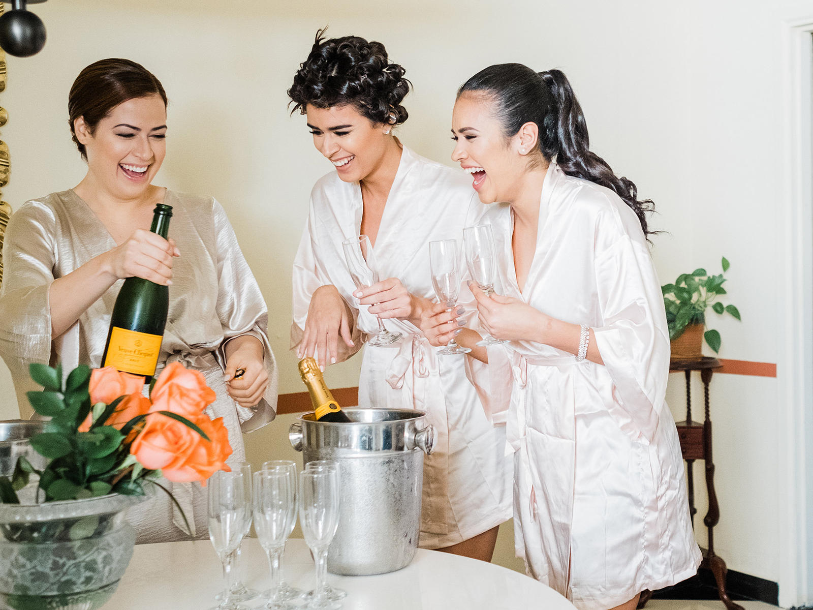 bride and bridesmaids serving champagne while getting ready