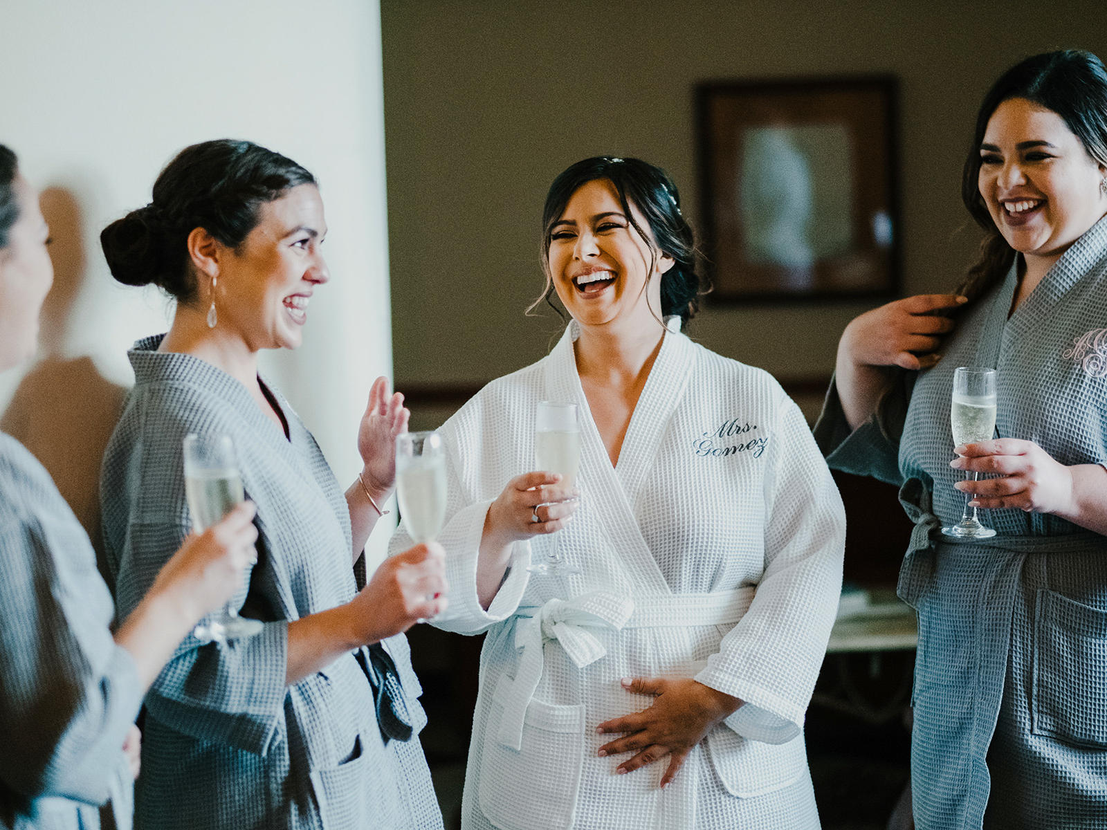 bride and bridesmaids in robes with champagne