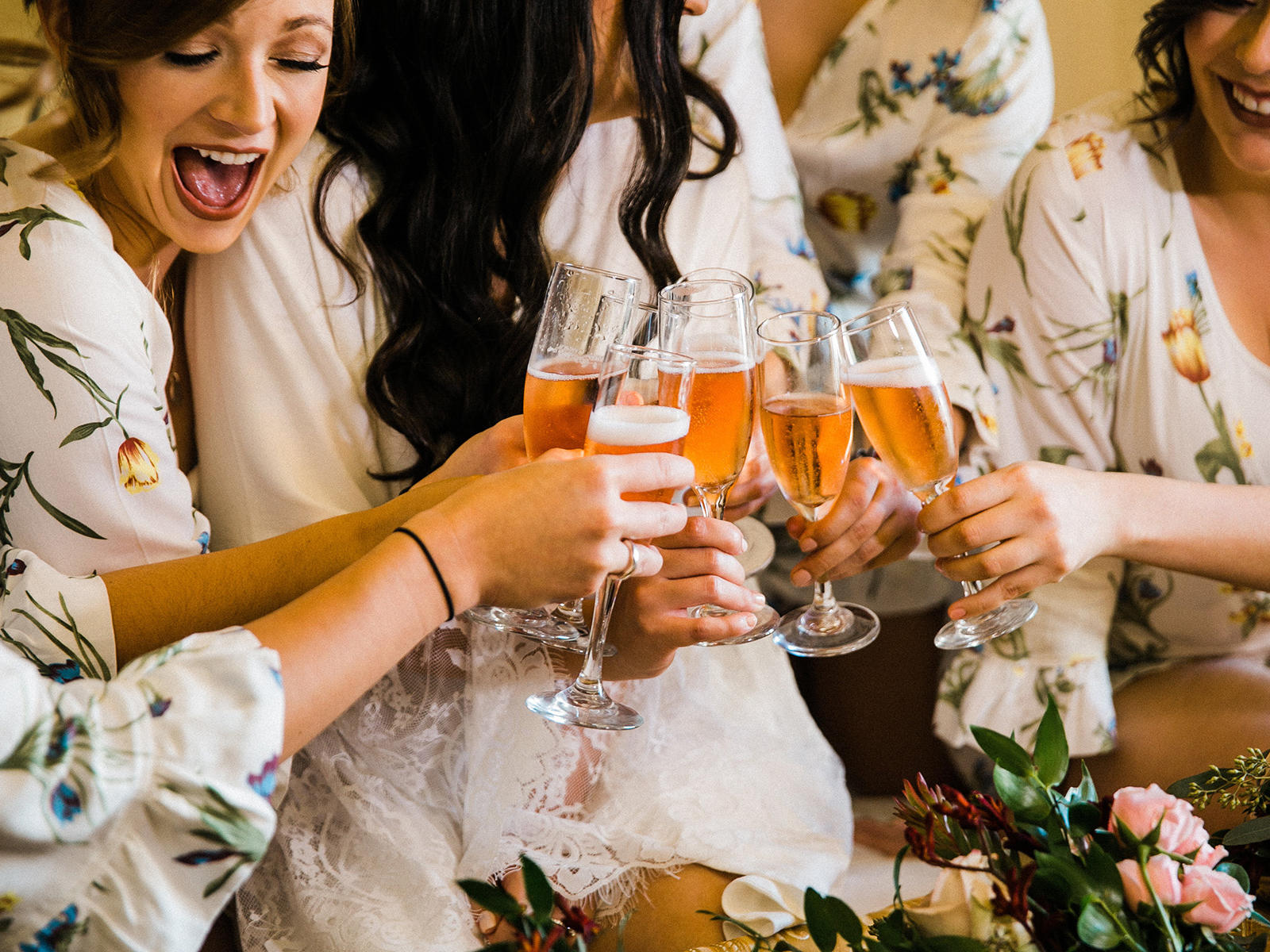 bridesmaids and bride cheering with mimosas in bed