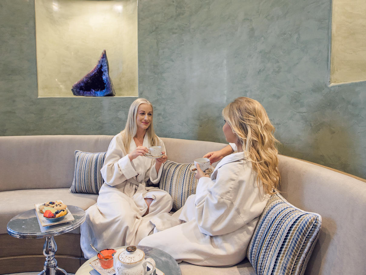 Two women in robes lounging and drinking coffee.