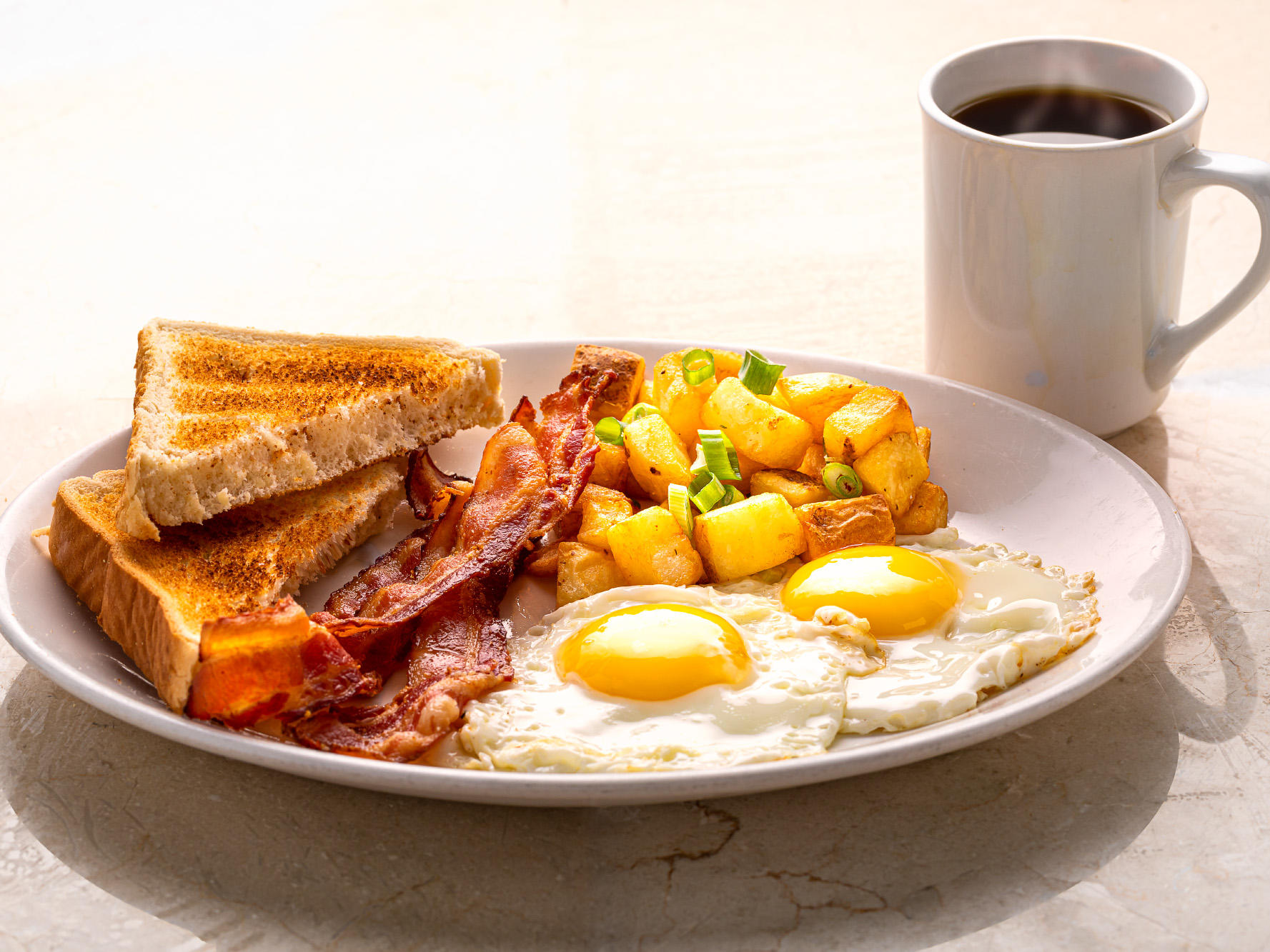 fried eggs, potatoes, bacon and toast with coffee