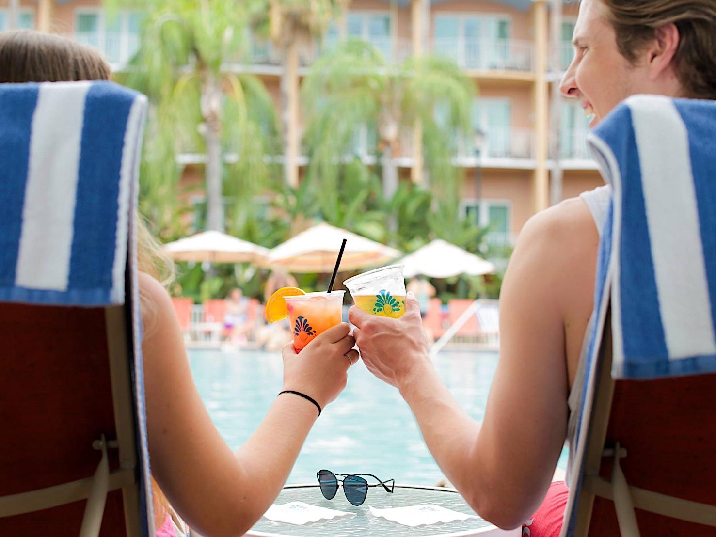 Two pool-goers clinking glasses by an outdoor pool.