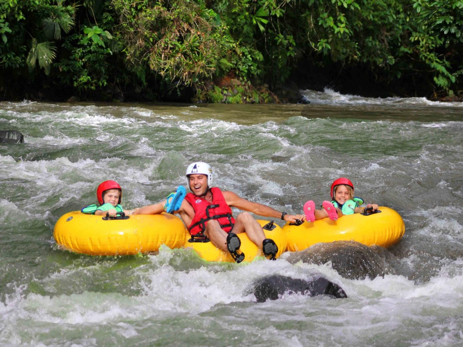 three guests tubing down river