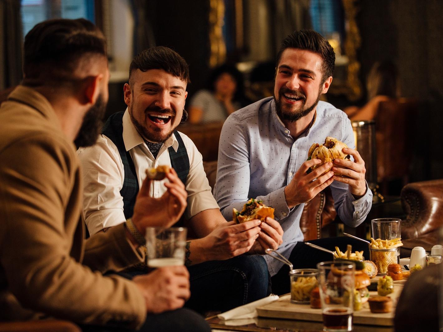 Gentlemen at a bar eating burgers.