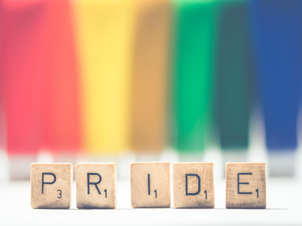 scrabble letters spelling Pride with rainbow colors blurred in background