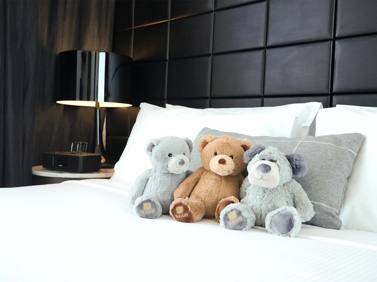 Three Teddy Bears on the Bed at Silkari Hotels