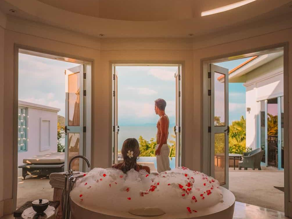 couple enjoying their stay at the pool villa which features a bathtub