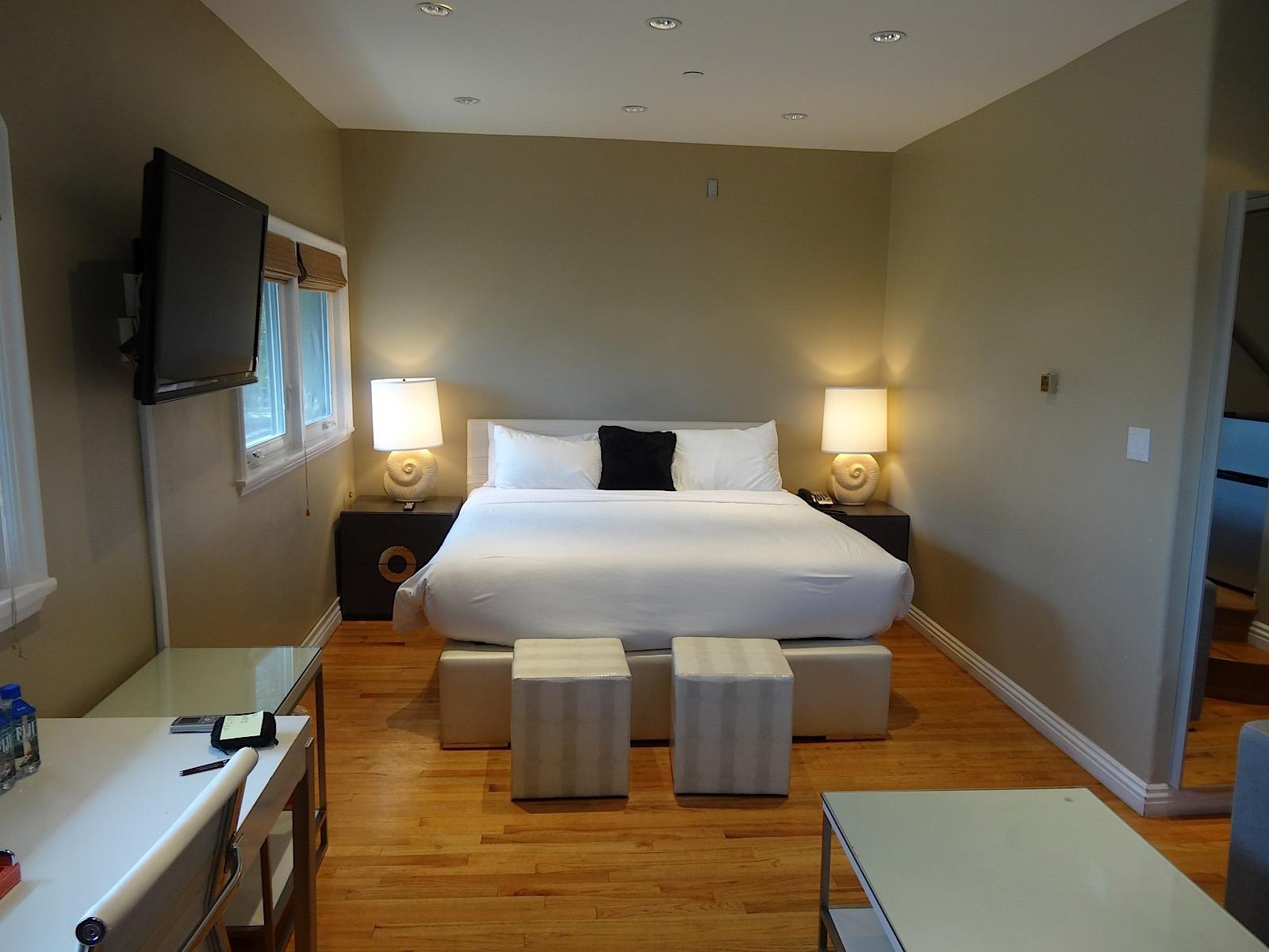 room with king bed, flat panel TV and desk