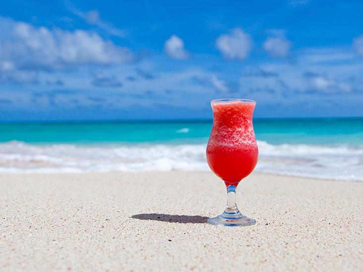 red frozen cocktail on beach sand