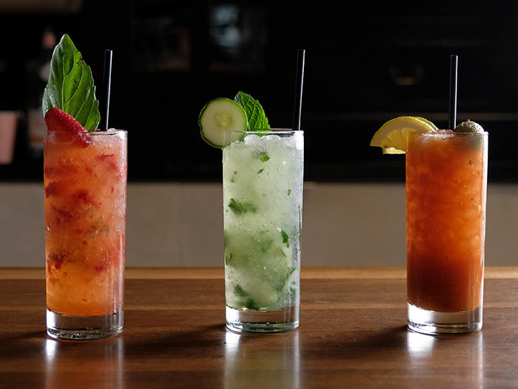 three assorted cocktails on table