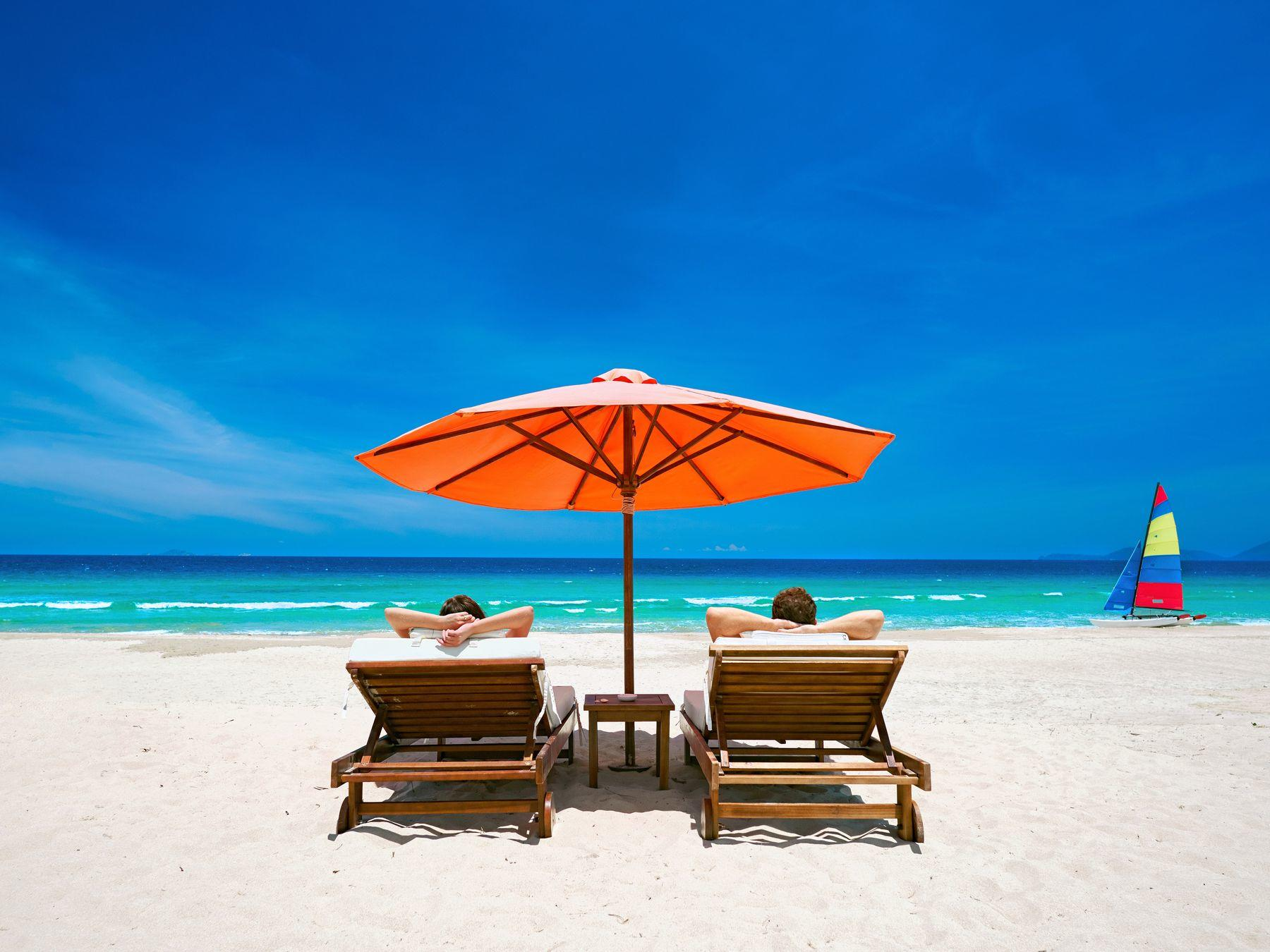 couple lounging under orange umbrella on beach with bright blue skies
