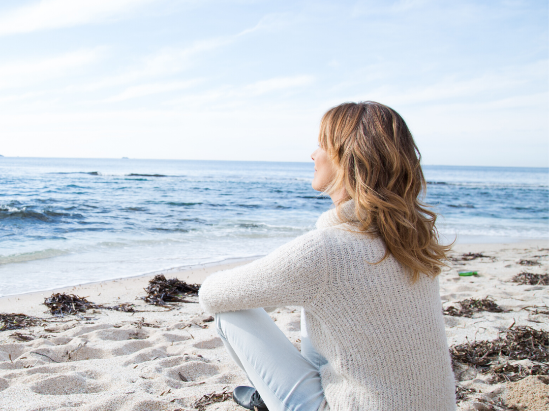 Woman on beach in cozy sweater