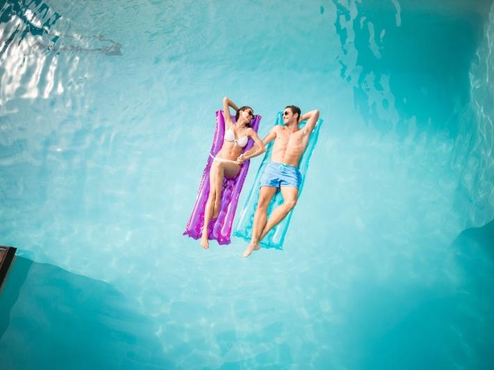 Couple floating in a pool