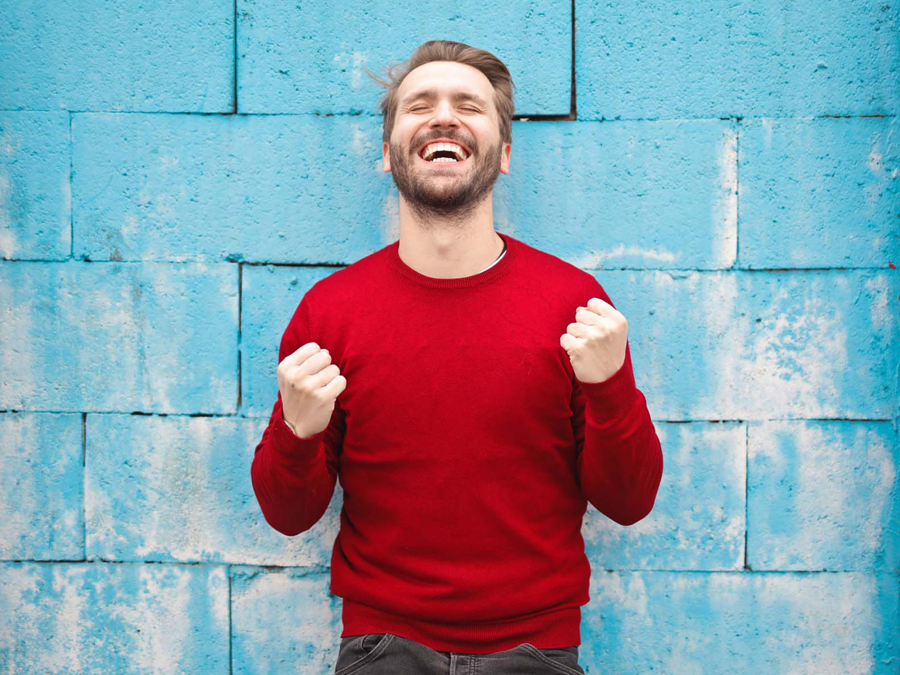 Man excited with fist clenched standing against blue brick wall