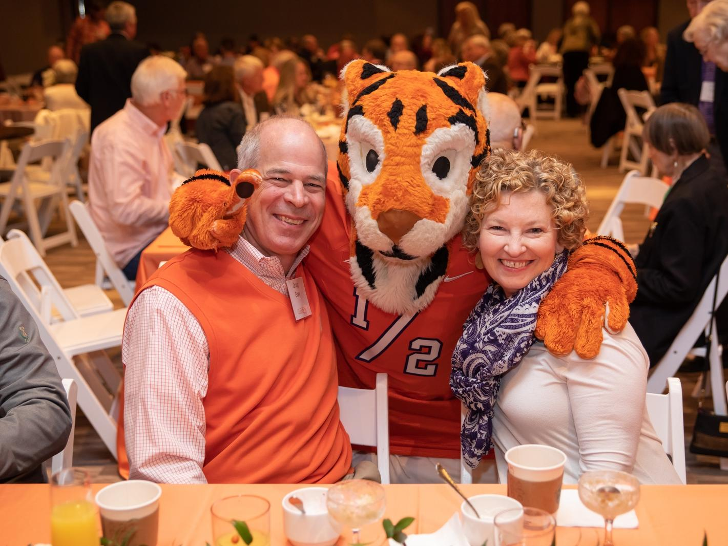 tiger mascot posing with couple