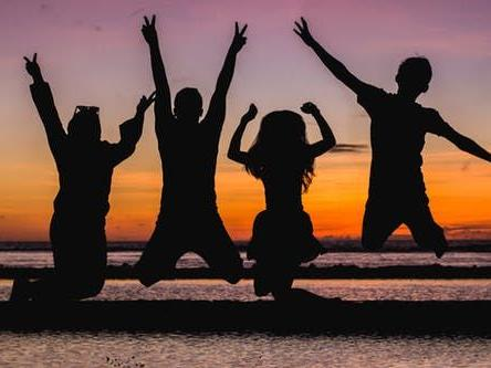 A family jumping in joy with the sun setting at the back