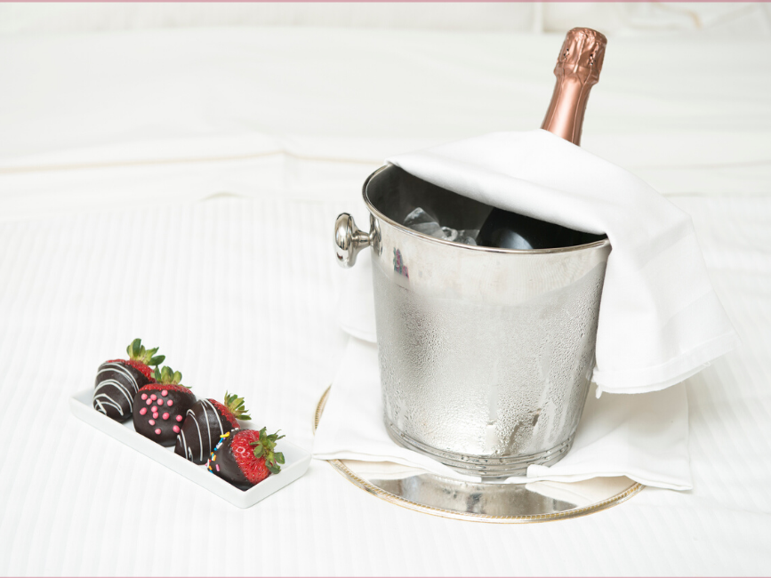 Bottle of champagne in ice bucket and chocolate coated strawberries