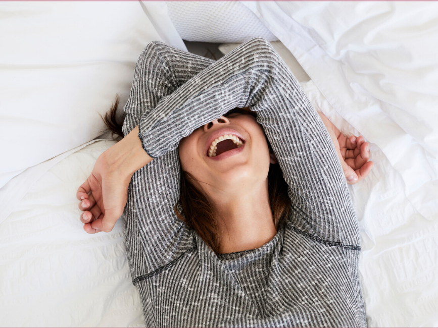 Girl laughing with arms over face