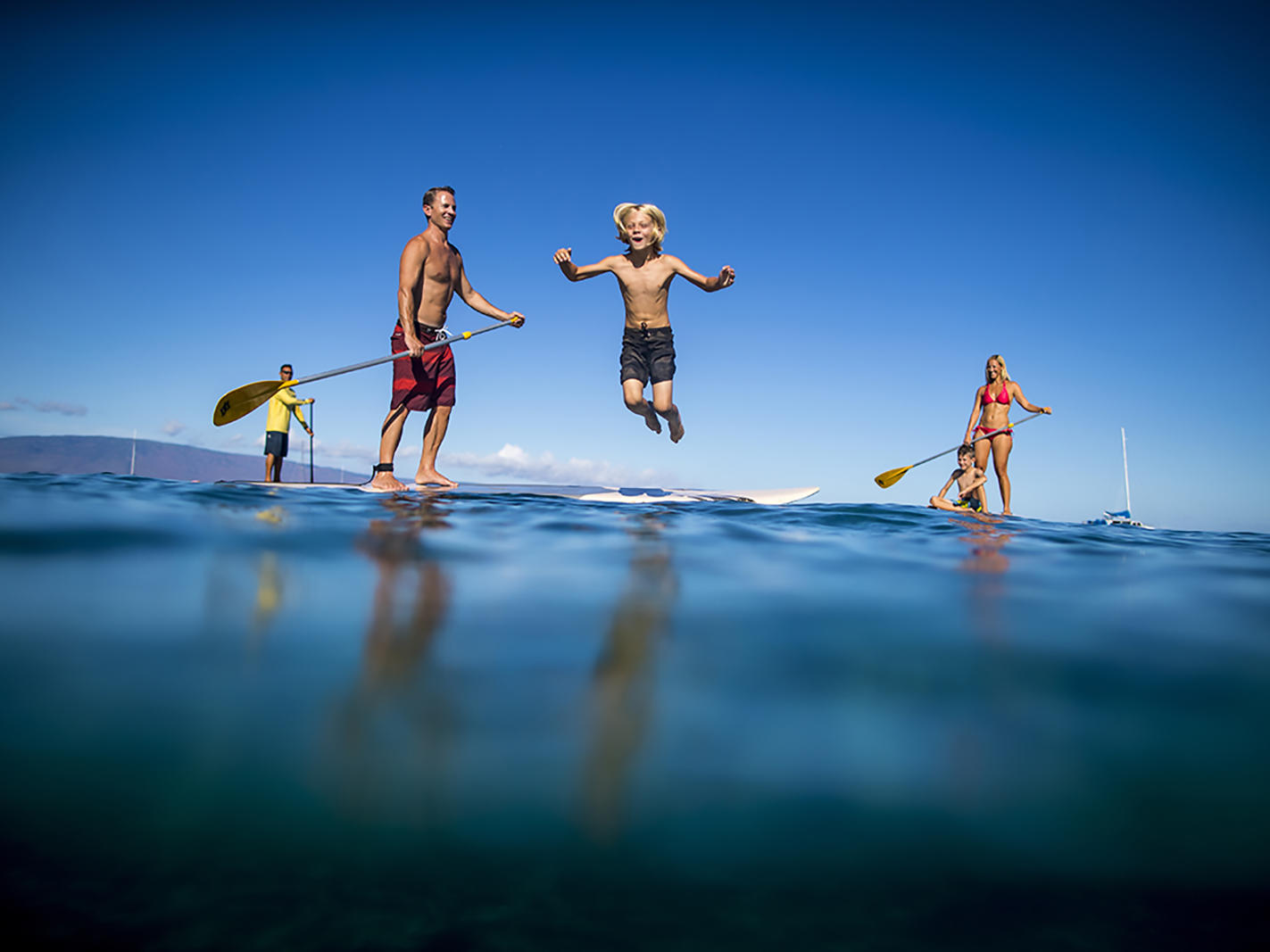 boy jumping off paddleboard