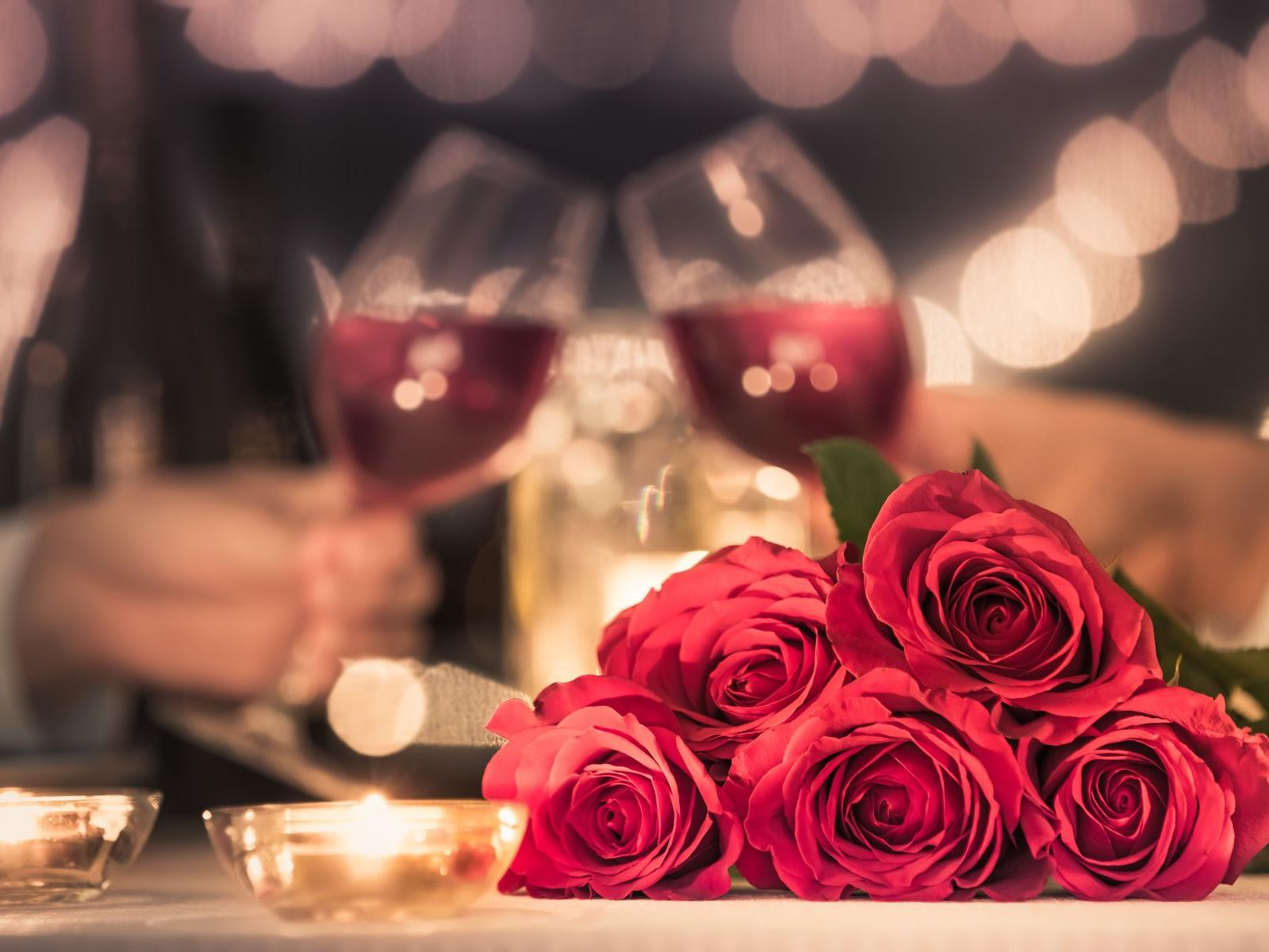 Bundle of roses with wine glasses clinking in the background.