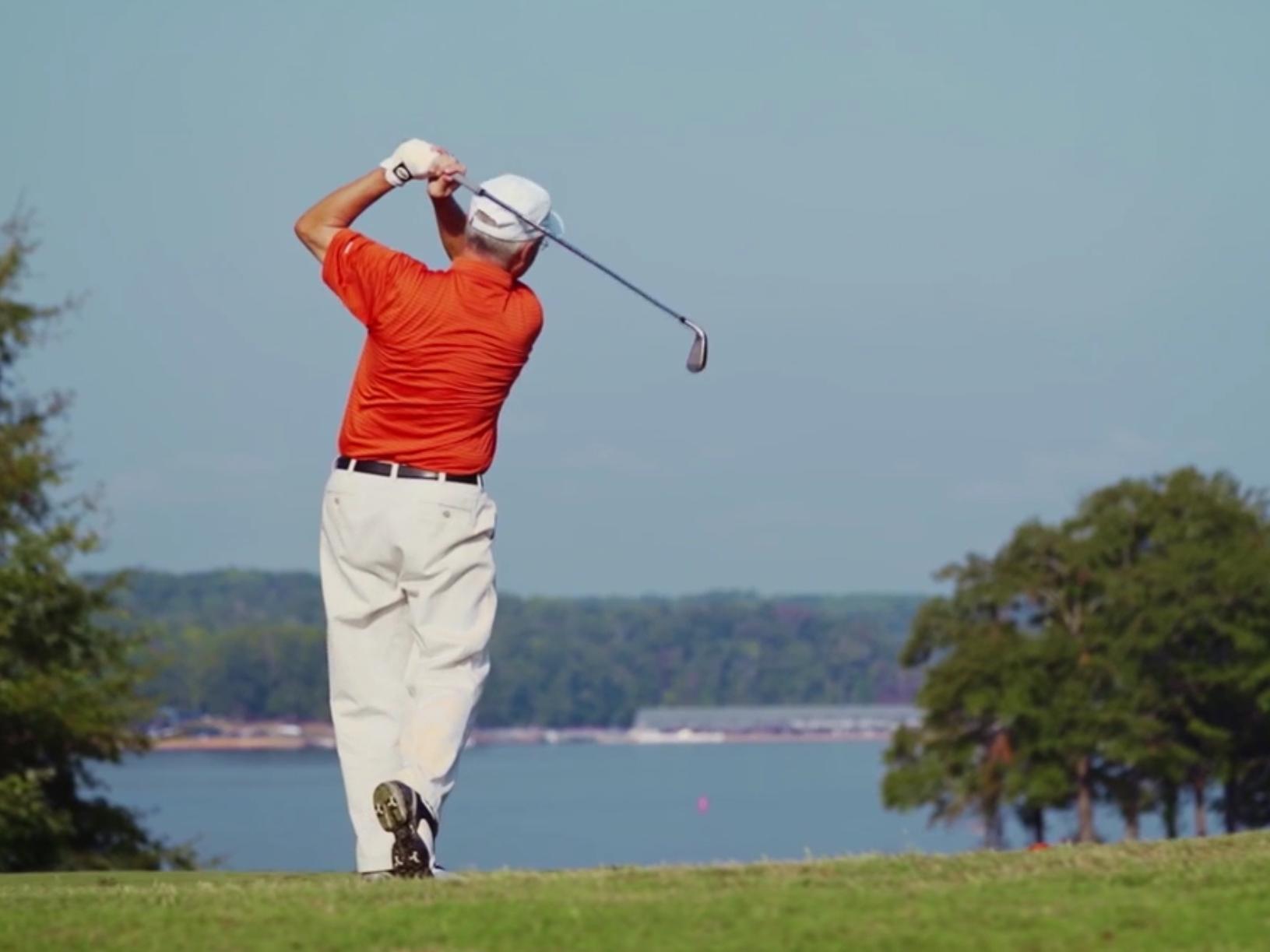 man golfing in orange polo