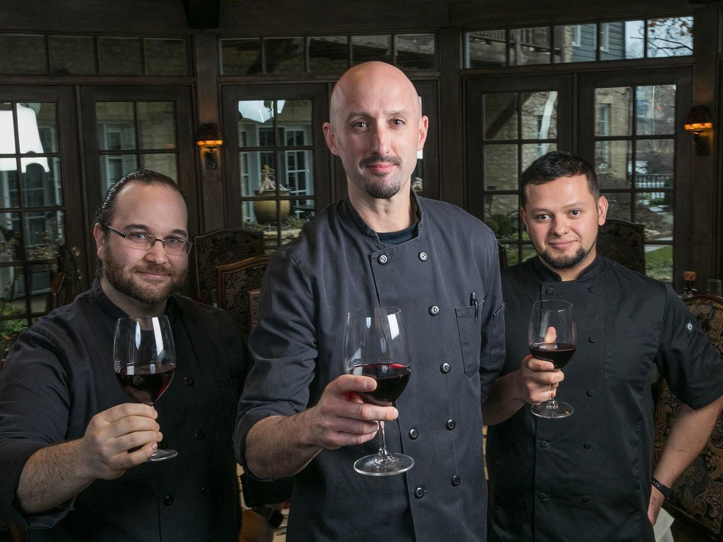 three chefs holding glasses of red wine